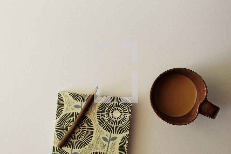 pencil on a journal and a coffee mug