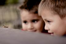 two little boys watching a caterpillar
