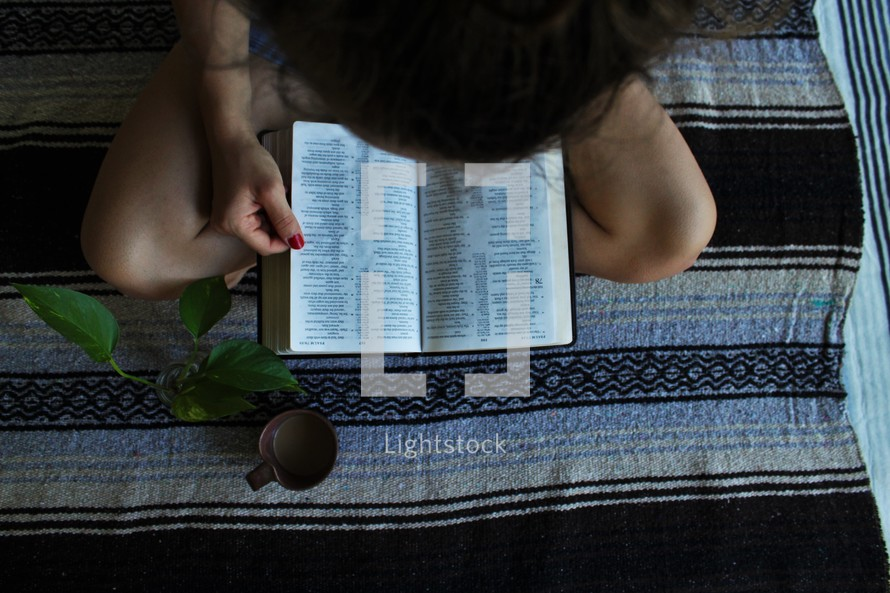 a girl reading a Bible and writing in a notebook