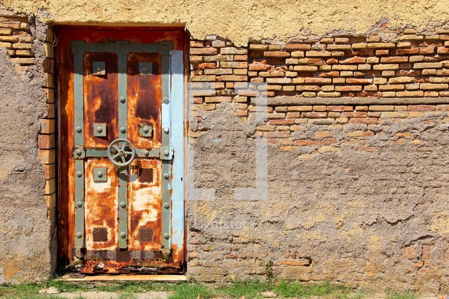 Old rusted vault door in weathered brick wall