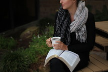 a woman holding a mug with a Bible on her lap