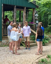 youth talking outdoors near a cabin at summer camp