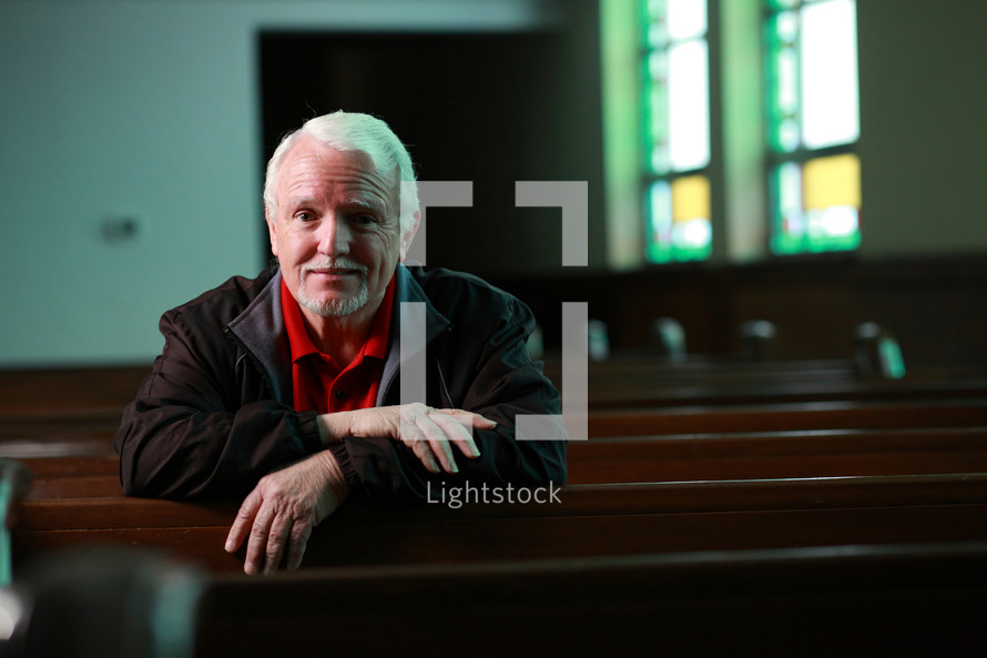 Senior adult man sitting in a church and looking directly into the camera with a happy expression on his face. Shallow depth of field with selective focus on his face.