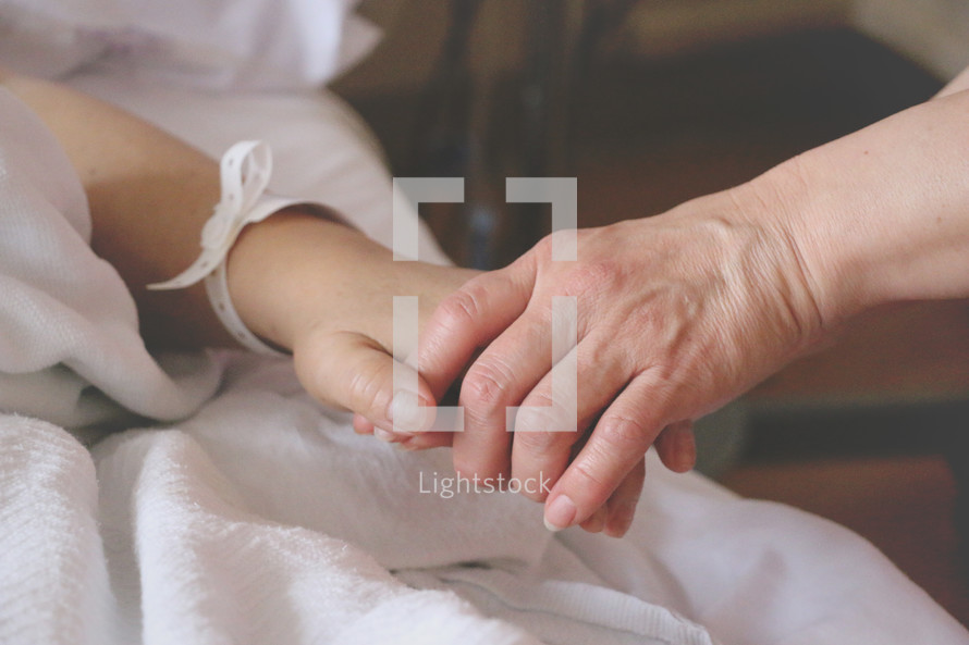 holding the hand of someone who is sick