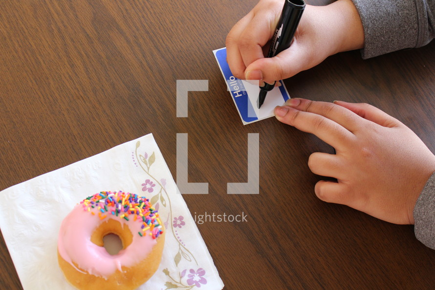 writing a name on a name tag and a donut on a napkin