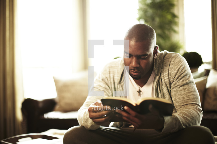 Man sitting, reading the bible at home