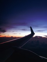 wing of a plane in flight at night
