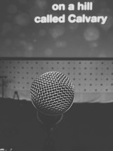 microphone and the words on a hill called Calvary on a projection screen