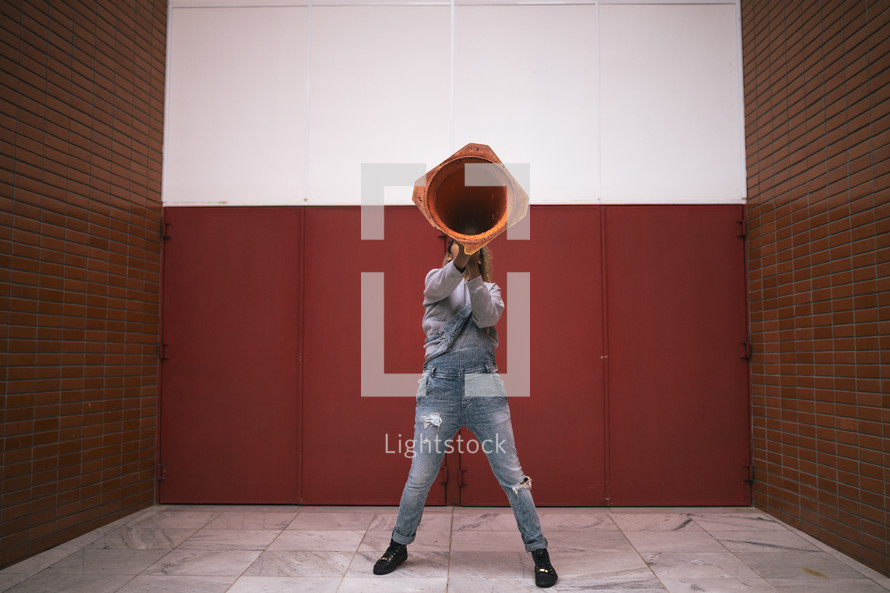 woman using a construction cone as a megaphone