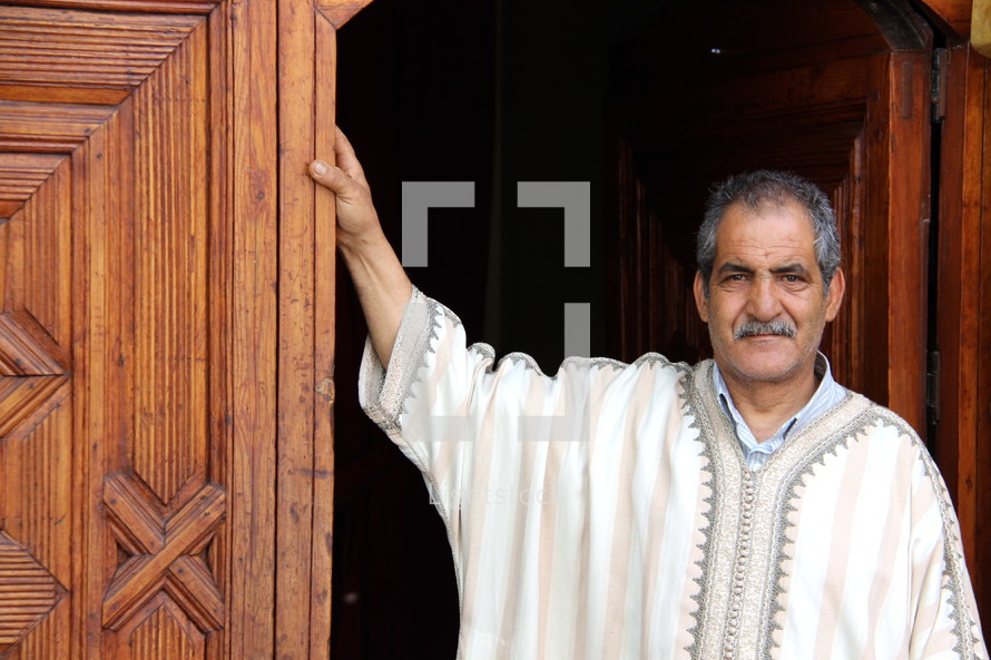 Moroccan man leaning against a wooden door [For similar search Ethnic Smile Face]