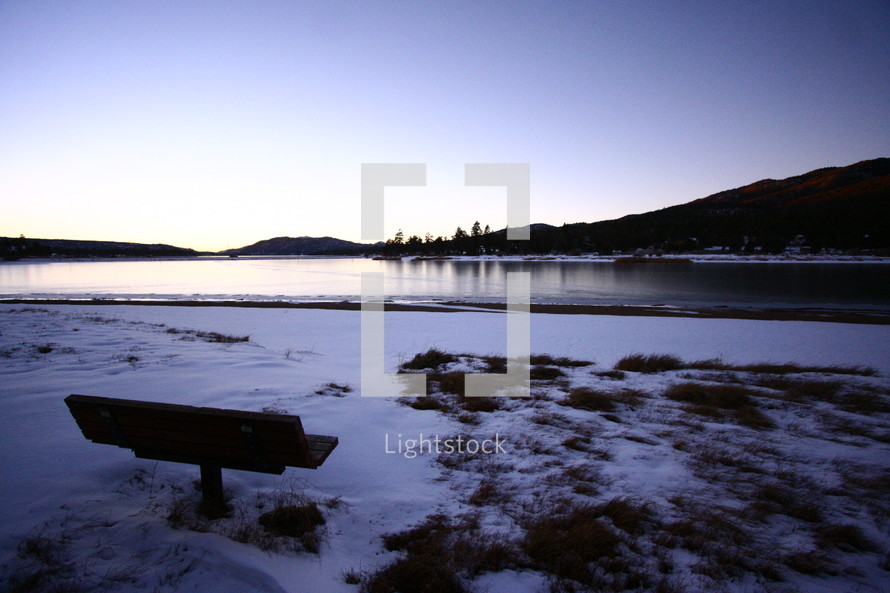 park bench in front of a lake on snow covered ground