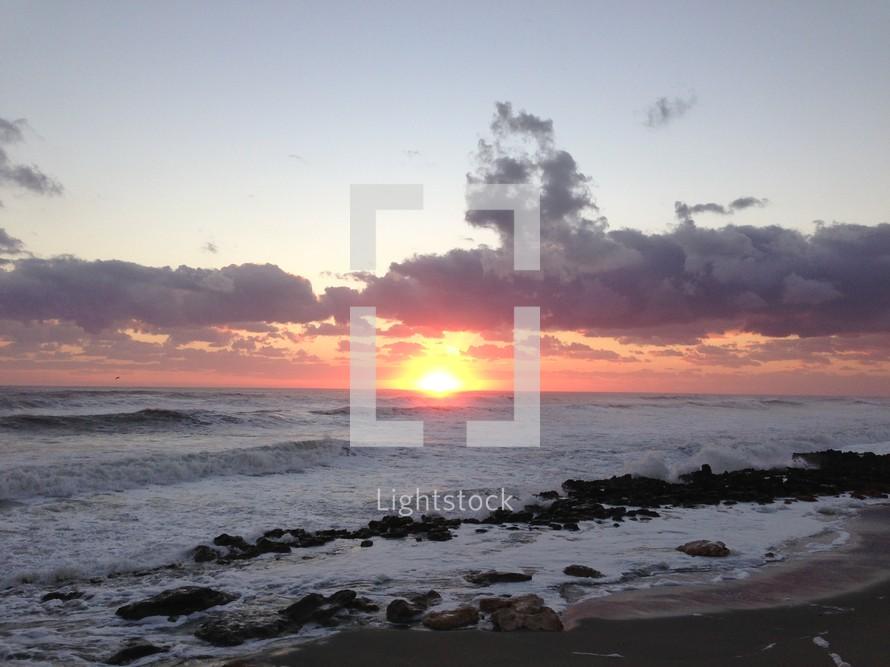 sunset over the ocean an a rocky beach