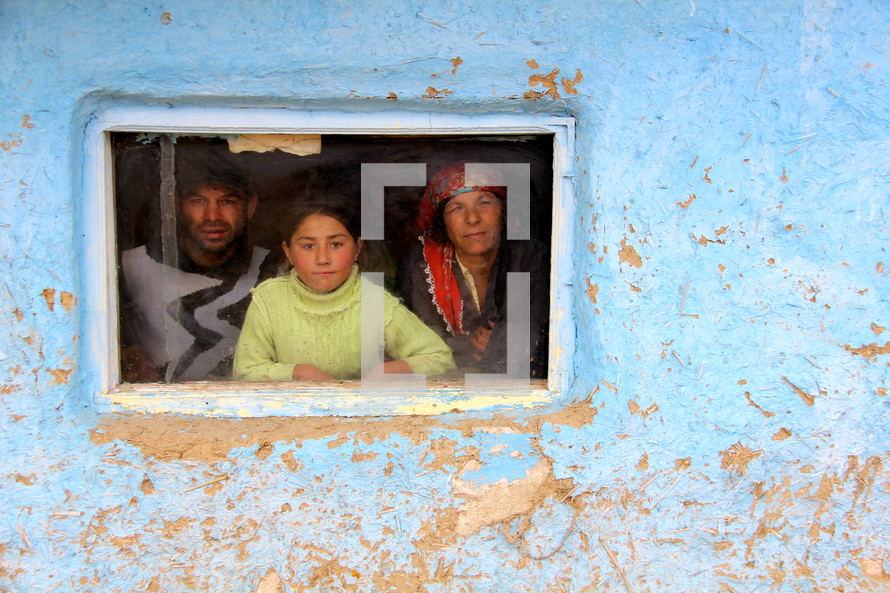 A Romanian Gypsey family looking through a window in their home