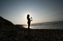 silhouette of a woman standing on a rocky beach holding flowers