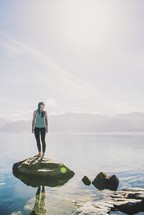 a woman standing on a rock by a lake