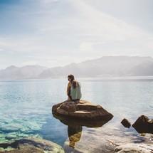 a woman sitting on a rock by a lake