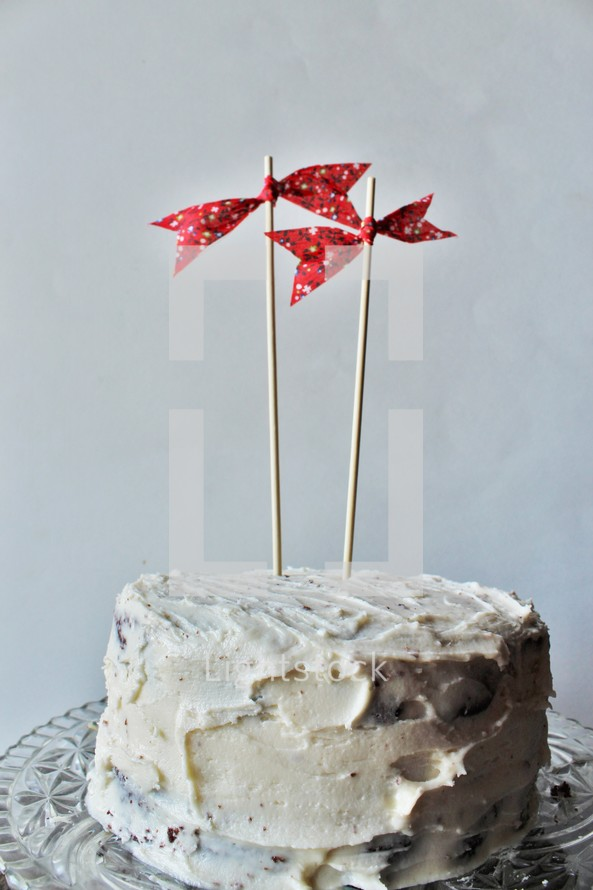 red bows on sticks on a cake