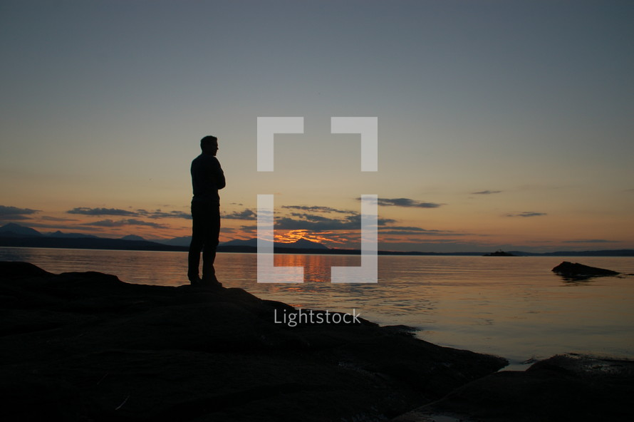 Silhouette of a man standing before a lake at sunset.