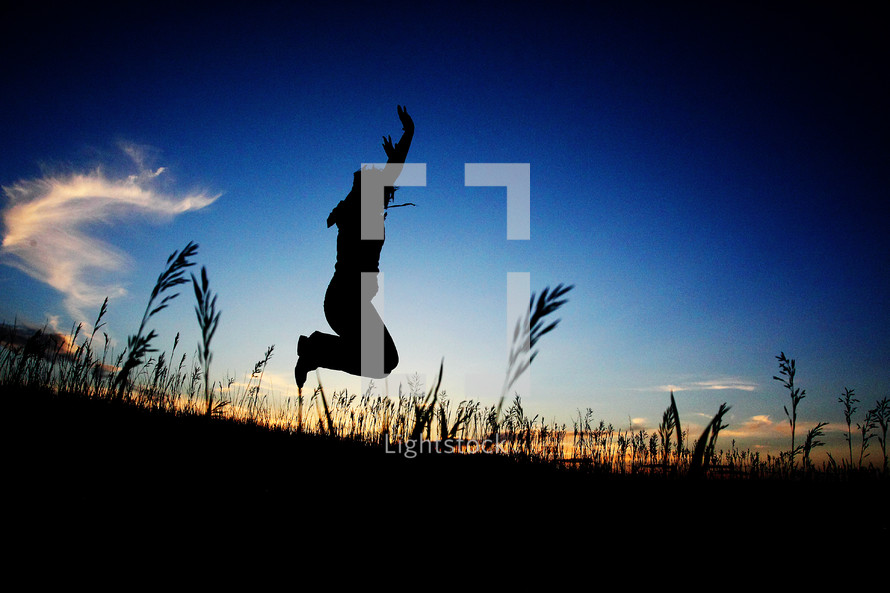 silhouette of a man jumping in a field