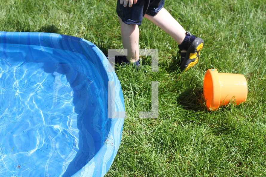 plastic pool in grass and toddler boy