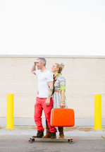 Couple standing on a skateboard holding suitcase