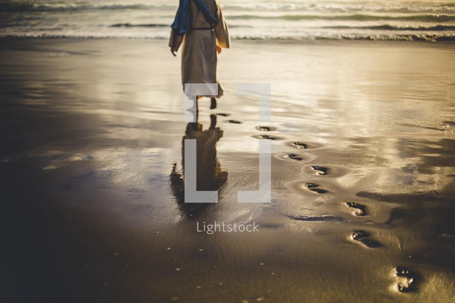 Jesus walking along a shore leaving footprints in the sand