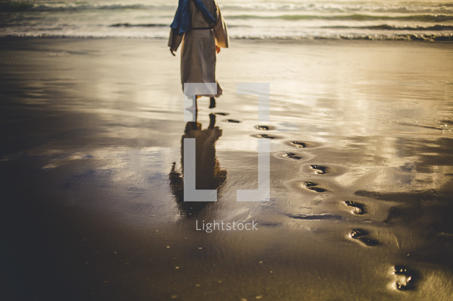 Jesus walking along a shore leaving footprints in the sand