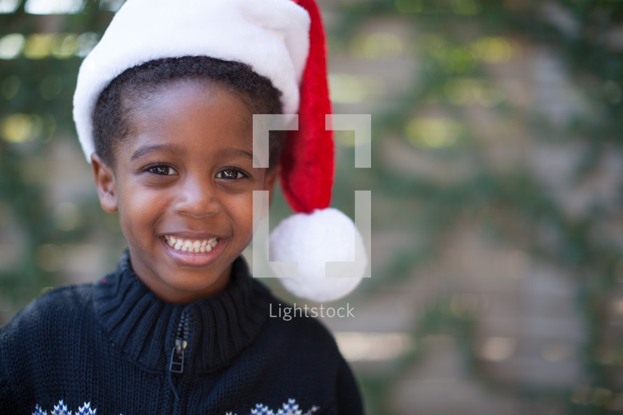 an African American boy child in a Santa hat