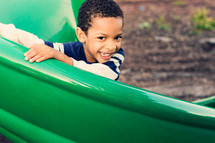 Smiling boy on a playground slide outside.