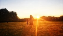 a mother and child walking outdoors through a field at sunset