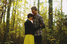a couple hugging in a fall forest