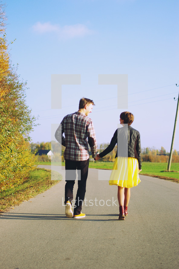 a couple walking holding hands down a rural street