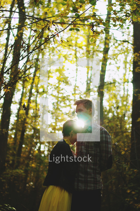 a couple standing together in a forest