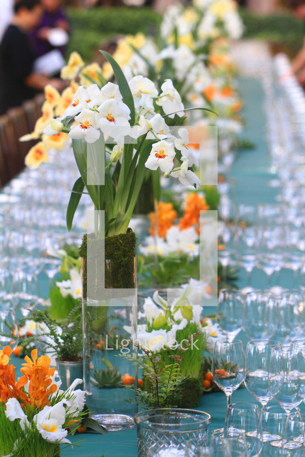 flower arrangements and wine glasses on a long serving table at a wedding