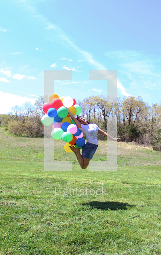 woman jumping up holding balloons