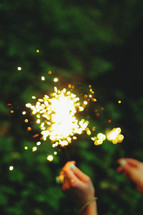 a woman holding up sparklers