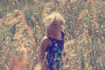 a toddler girl standing in tall grass