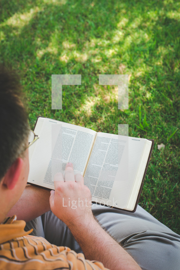 a man sitting in the grass reading a Bible
