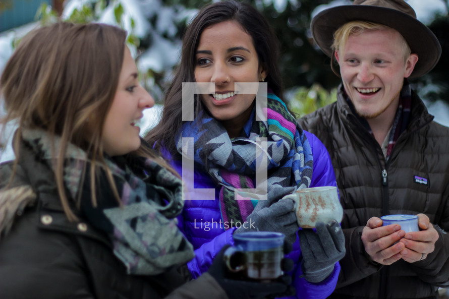 people standing outdoors in winter holding mugs
