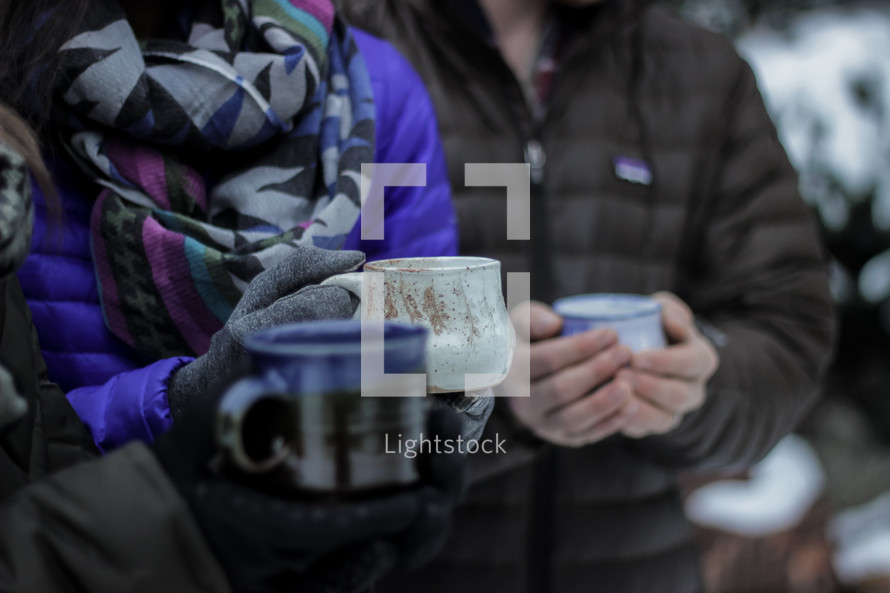 people holding mugs standing outdoors in winter