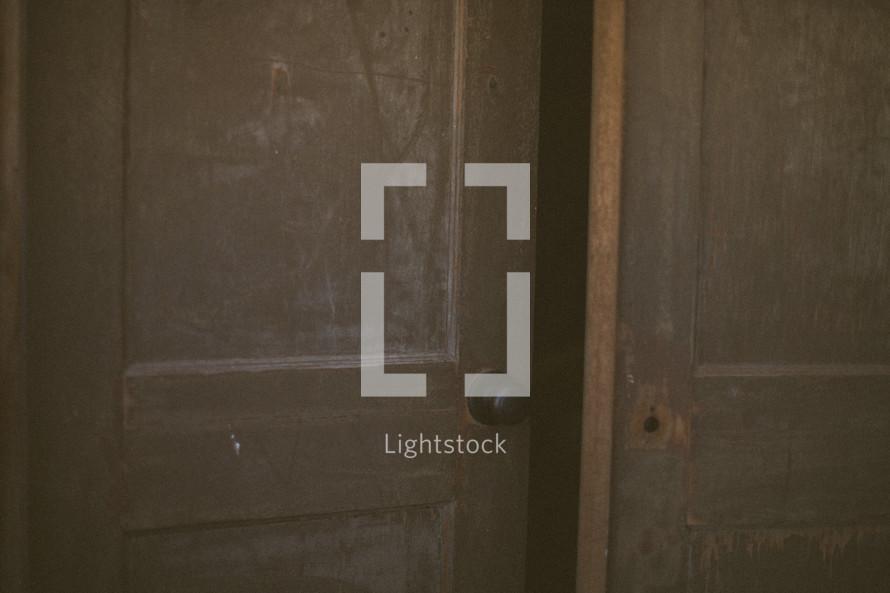 A wooden door cracked open