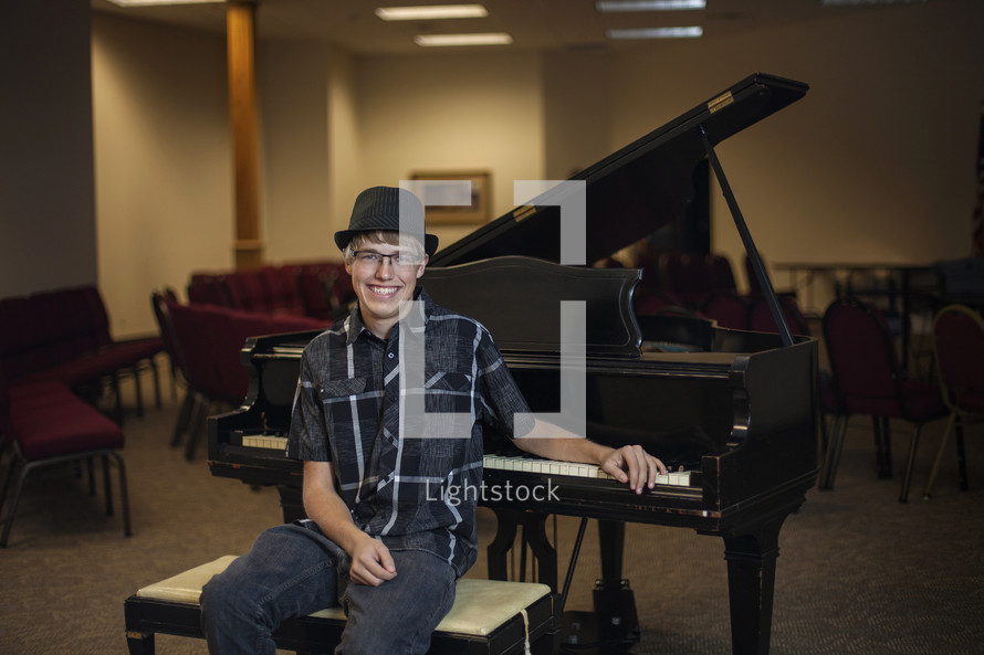 young man sitting with a grand piano