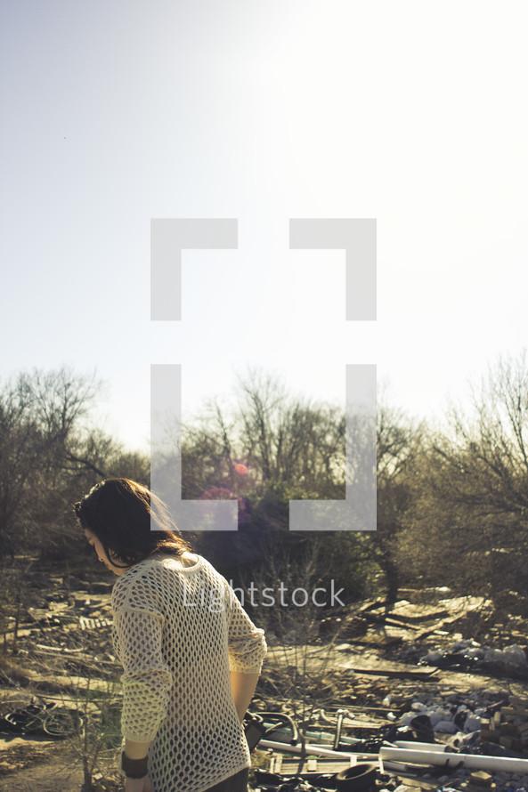 woman walking outdoors through debris