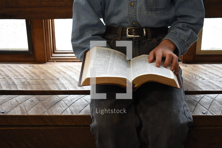 a man sitting reading a Bible