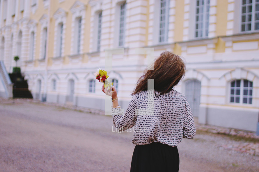a woman walking near a palace carrying flowers