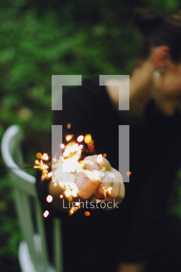 a woman holding a sparkler away from her face
