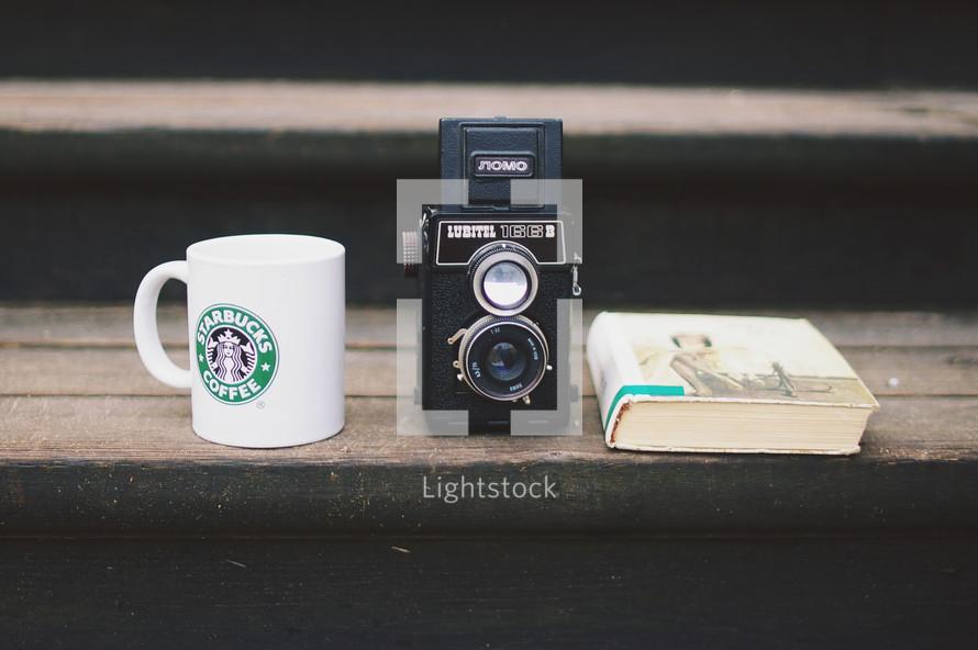 Starbucks mug, vintage camera, and book on a wood step