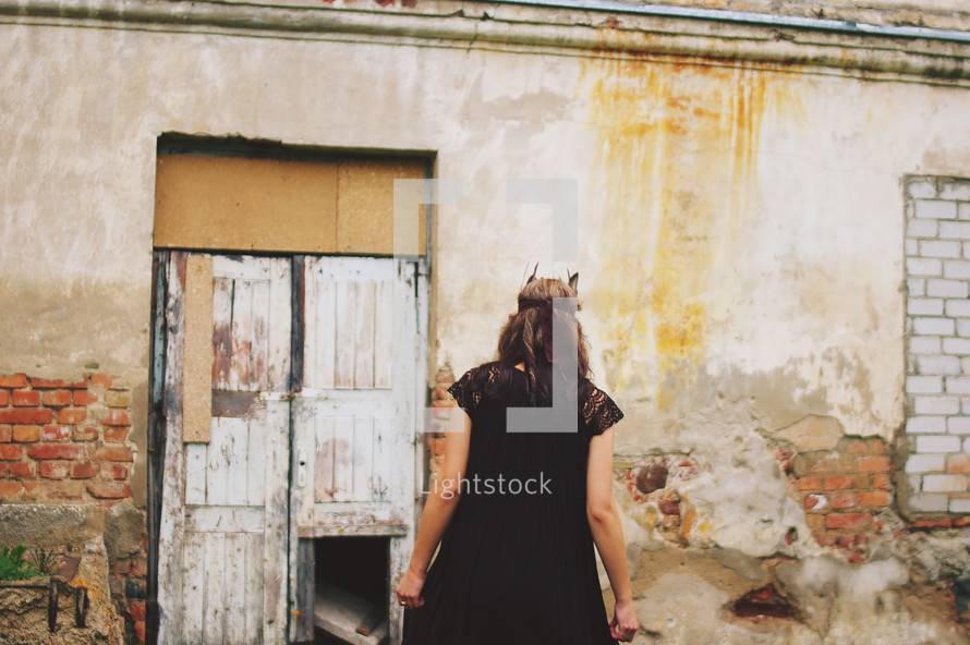 a woman wearing a Native American headdress walking towards an abandoned building