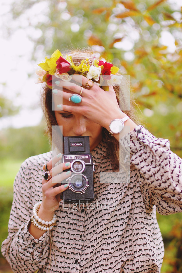 a woman with flowers in her hair holding a vintage camera