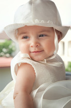 child a few months with white dress and hat on the day of her baptism